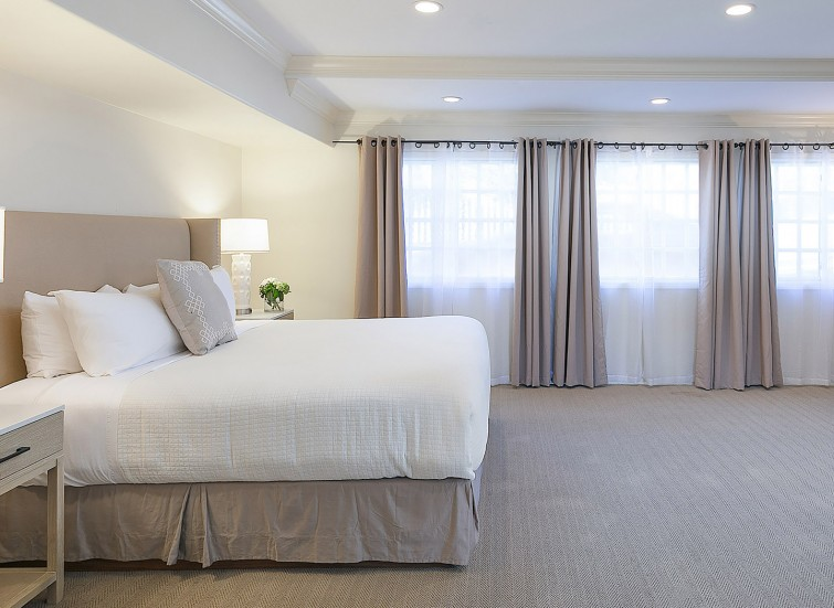 a guest room with white bedding