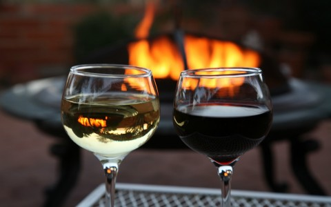 Glasses of wine in front of fire