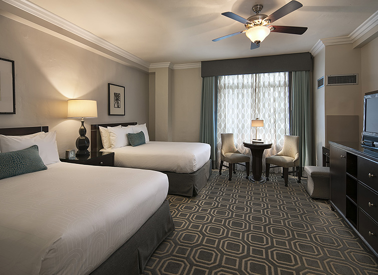 room with two beds accent pillows and a fan above