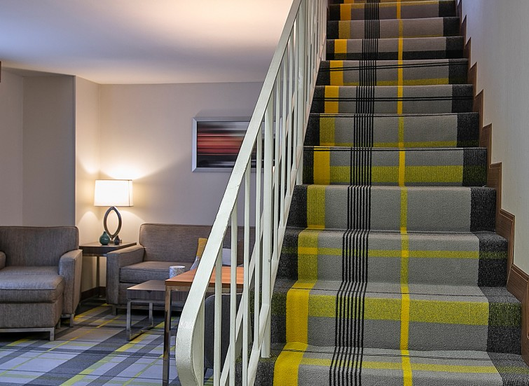 stairs with gray and yellow plaid carpet