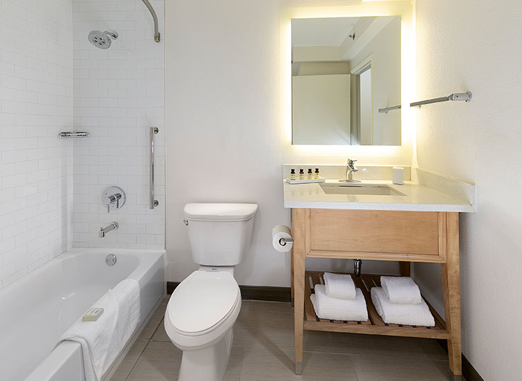 hotel bathroom with towels and ADA bathtub