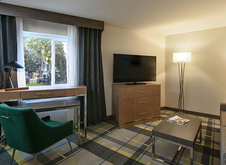 hotel suite with plaid carpet floor and green lounge chair