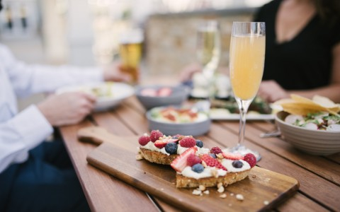 brunch toast with fruit toppings and mimosa on table