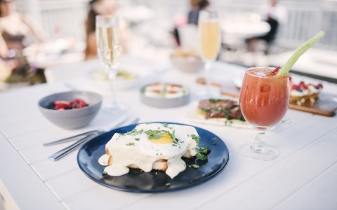 plated sunny side up egg on bread with a bloody mary drink on whit table