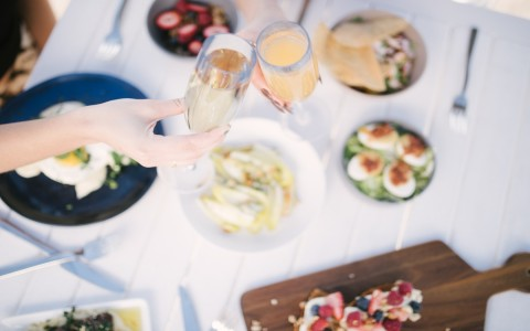 two people cheering mimosas with brunch food laid on table