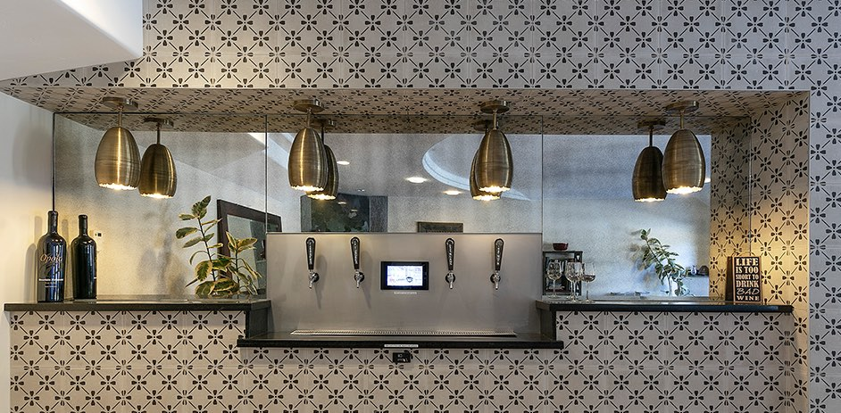 wall of beer taps with tiled wall