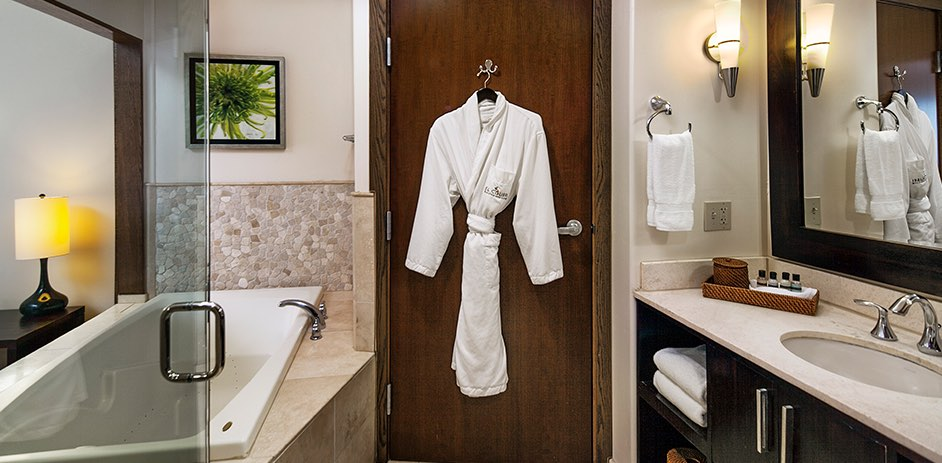 a spa inspired guest bathroom with a robe on the door