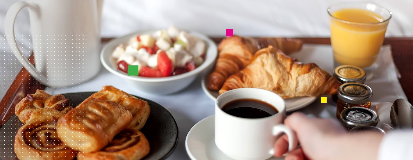 breakfast tray including coffee, orange juice, croissants and mixed fruit