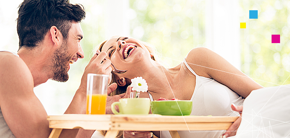Man and woman eating breakfast in bed