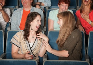 girls laughing in theater