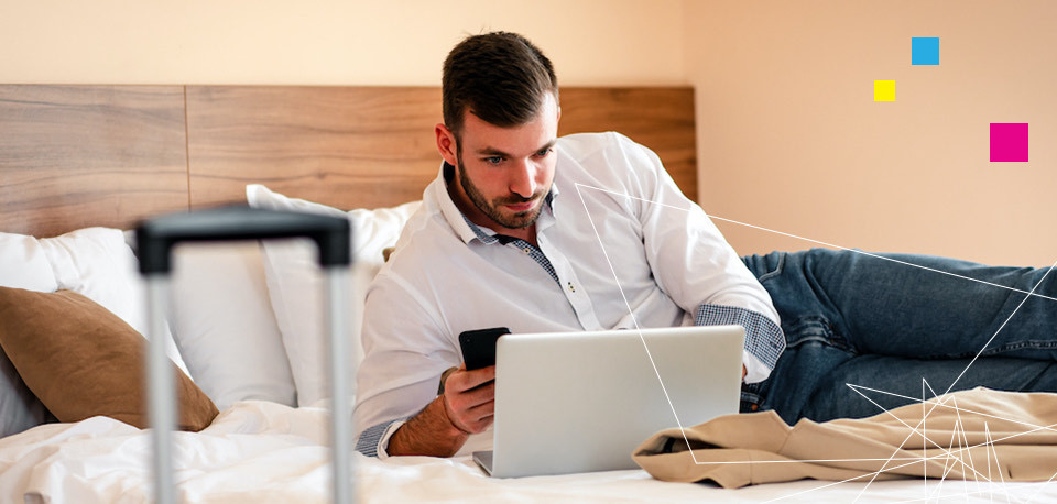 a man looking at a laptop screen while laying on a bed