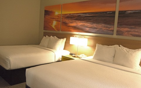 two hotel beds with a long panoramic of the sunset as a headboard