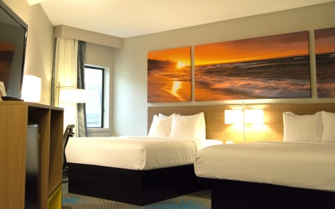 two beds with three paintings of a sun setting behind the bed