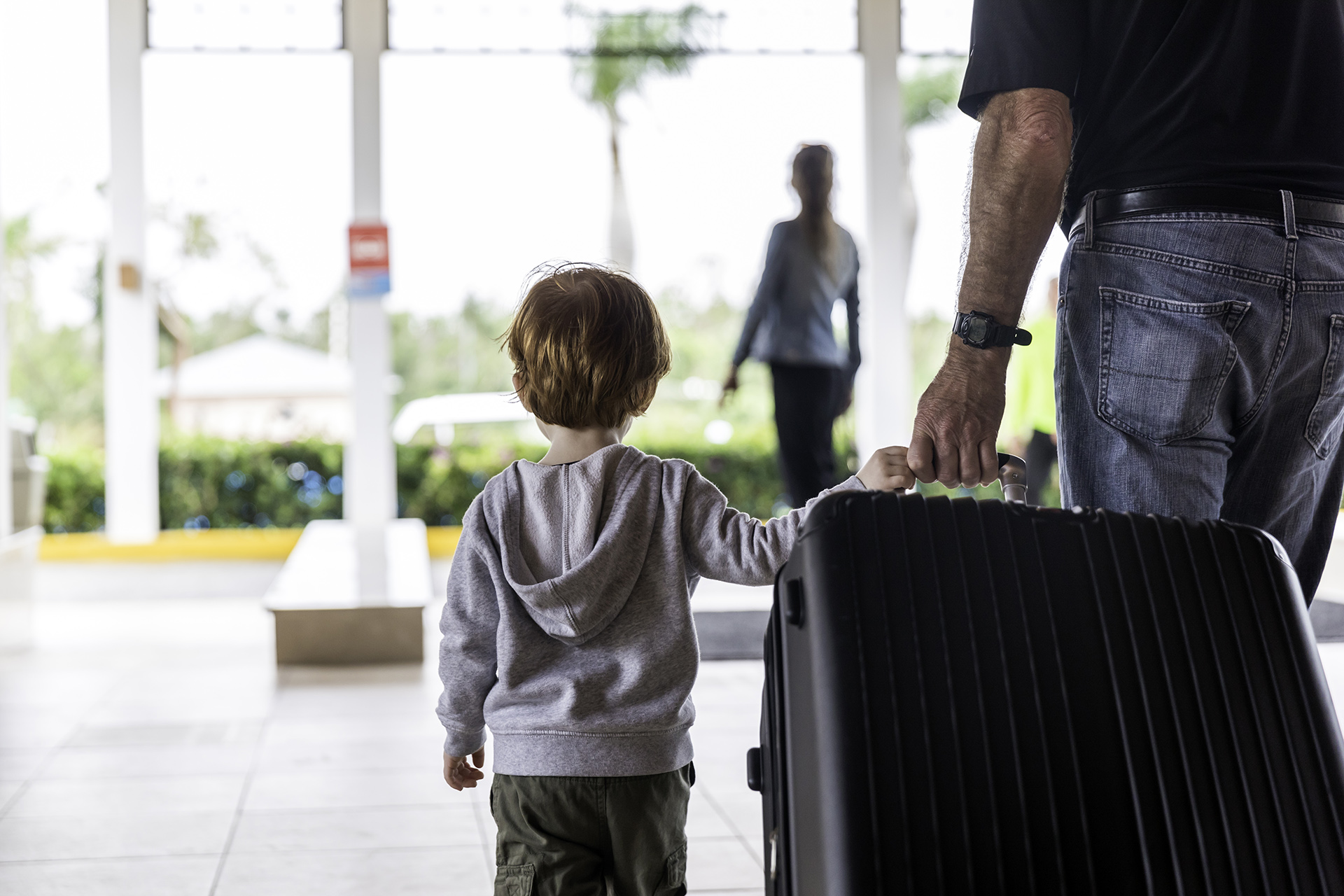 little boy and dad wheeling a large suitcase out of a hotel