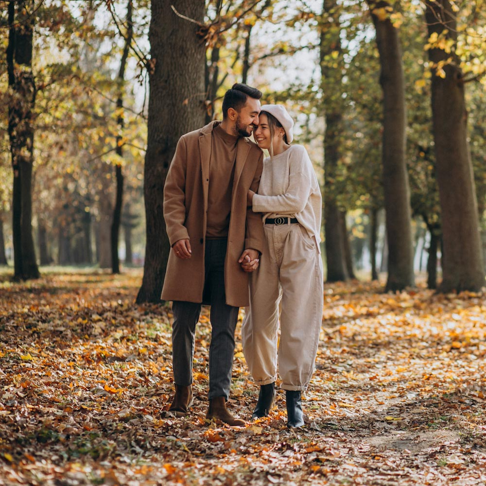 couple walking through fall forest