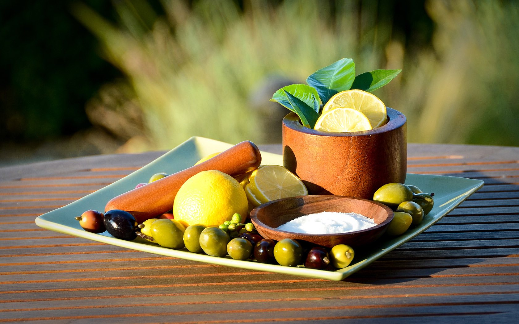 Lemons, lemon slices, olives and wooden bowls arranged on a table