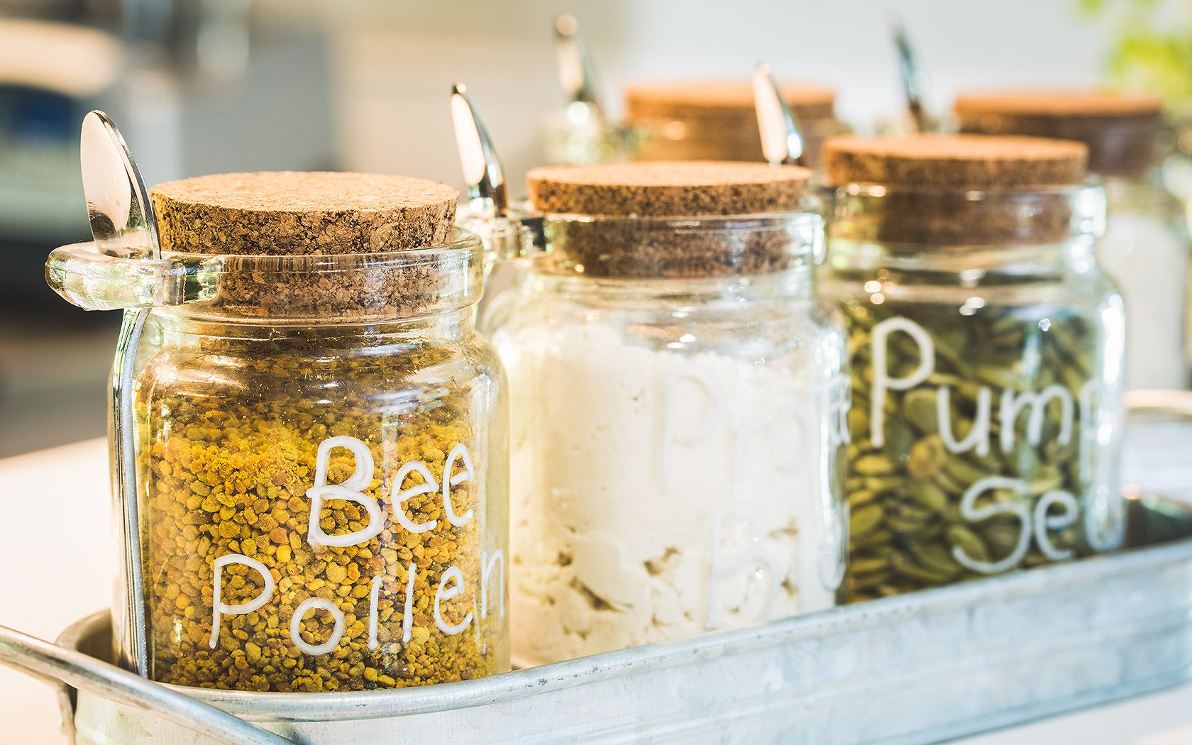 Closeup of three mason jars, one has bee pollen in it and another has pumpkin seeds.