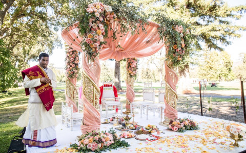A beautiful Floral display of the alter at an Indian Wedding with peach and soft orange colors