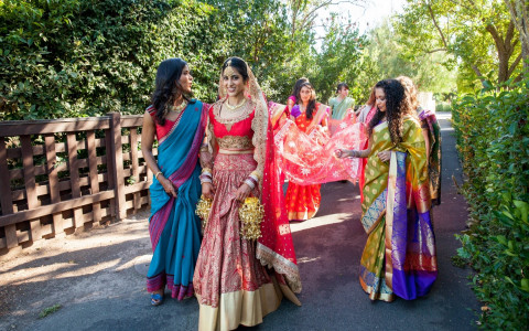 View of bride and bridesmaids walking up to aisle in beautiful Indian dresses