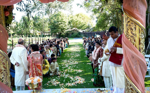 View of an Indian wedding ceremony overlooking the guests and the flower pedaled aisle