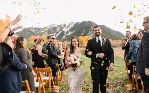 couple walking down aisle with mountains in background