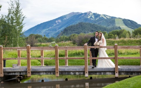 bride and groom on bridge with mountain background