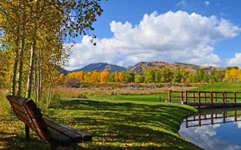 pond with bridge, park bench, and mountains in background