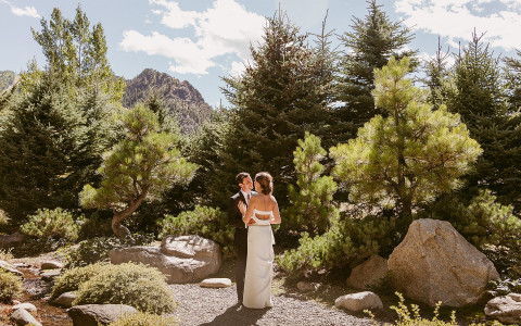 Couple in wedding attire outside surrounded by trees and mountains
