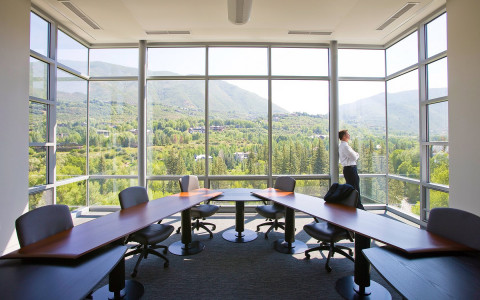 conference room with glass windows that show the green trees scenery