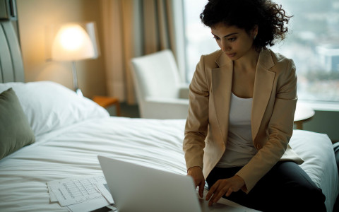 woman sitting on a bed working with laptop