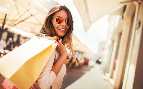 Woman with sunglasses smiling and holding yellow shopping bag