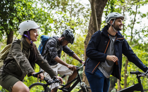 Three people on mountain bikes wearing helmets