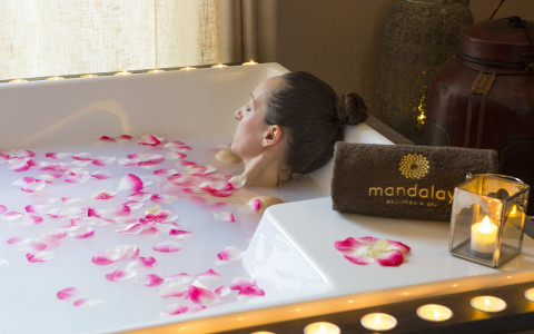 Woman relaxing in bathtub with candles and flower petals