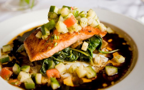 Salmon on bed of spinach and diced vegetables