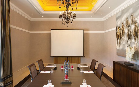 Meeting room with wooden table setup and projector screen on the wall