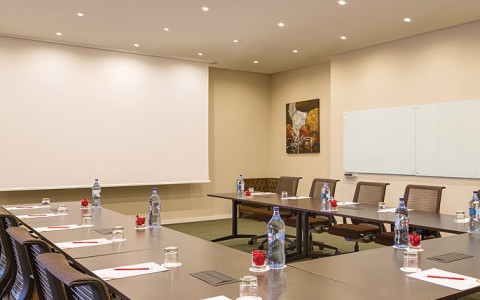 Meeting conference table set up in a u shape and facing a projector screen