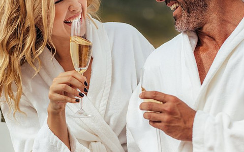 Man and woman wearing white robes drinking champagne