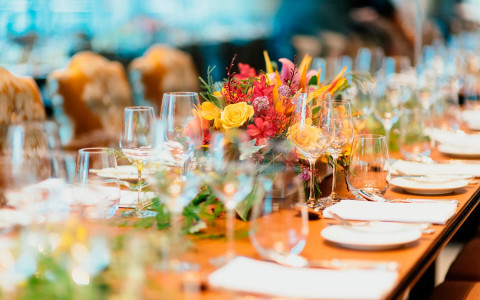 Event dining table set up with colorful flowers in the middle