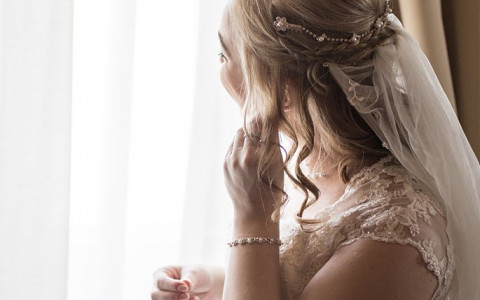 Bride looking out a window putting on earrings