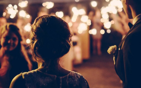 Bride and groom in front of a crowd at night