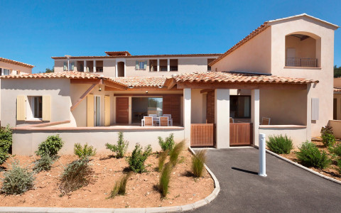 exterior of hotels bastides country house with patio and sand with bushes as landscape