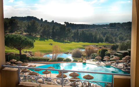 view of outdoor pool with lounge chairs and umbrellas with golf course, landscape, and mountains in background