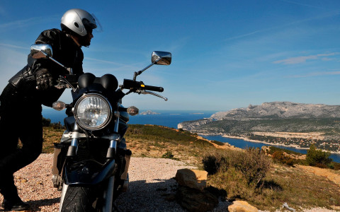 man leaning against his motorcycle looking at ocean and hills with rocks and grass