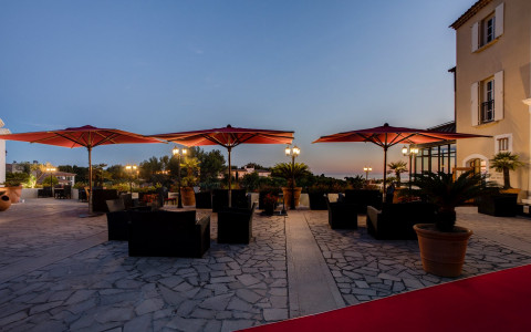 outdoor patio area with sofas, tables, and umbrellas while sun is almost set