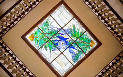 stained glass window with green branches and blue design on ceiling