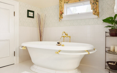white bathtub with gold accents