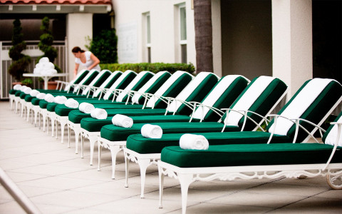outdoor pool lounge chairs with green cushions and white rolled up towels