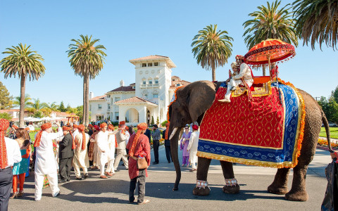 elephant dressed in lavish red, blue, and yellow attire with two people riding it on the street. Many people dressed in lavish Indian attire are surrounding the elephant and there is a white building in background.