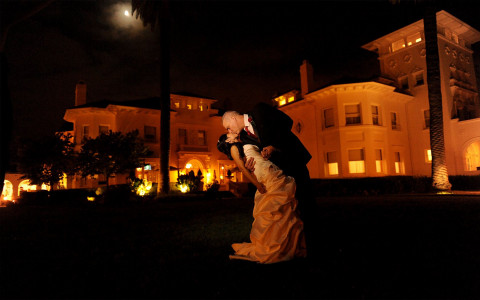groom dipping bride and kissing her in front of building that is lit up in orange at nighttime