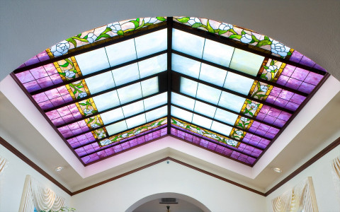 stained glass window that has purple and flower design is vaulted on the ceiling